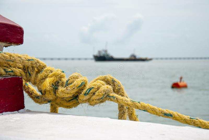 Closeup detail of rope tied to the nautical support to hold a boat stock photo