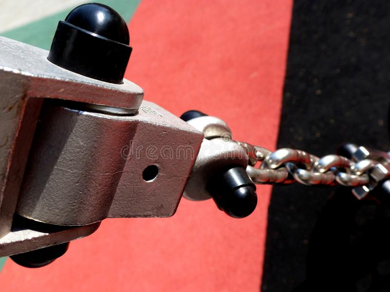 Closeup detail of shiny steel chain swing hanger. Macro detail of shiny steel swing chain and connection in diminishing perspective with blurry colorful stock photos