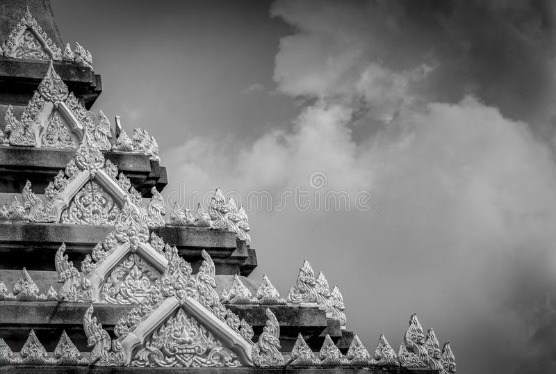 Closeup detail of temple in Thailand. Art pattern. Traditional Thai style sculpture against clouds and sky. Black and white scene royalty free stock photo