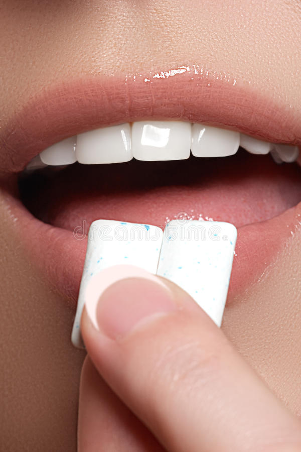 Closeup detail of woman putting pink chewing gum into her mouth. Chewing Gum, Eating, Women. Close up on a beautiful girl stock photo