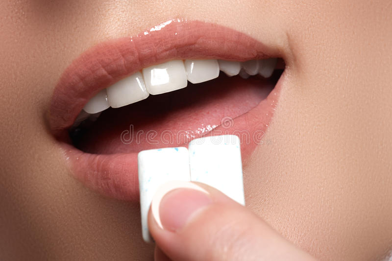 Closeup detail of woman putting pink chewing gum into her mouth. Chewing Gum, Eating, Women. Close up on a beautiful girl. While enjoying a candy stock photo