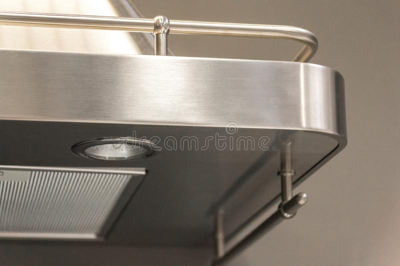 Closeup of details of buttons on a metal exhaust fan with light in a luxury kitchen. royalty free stock photo