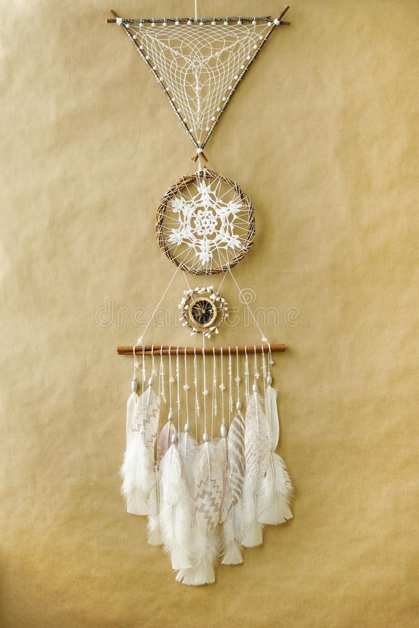 Closeup details dreamcatcher with painted silver light pink feathers on craft paper background stock photos