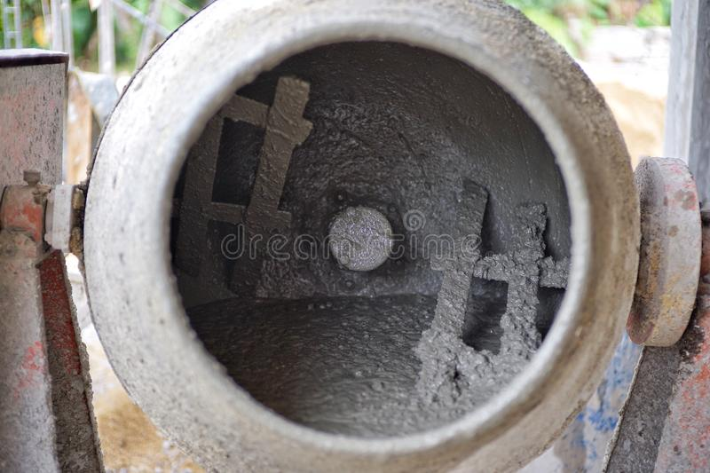 Closeup dirty concrete mixer with cement and ingredients inside. At the construction site stock photo