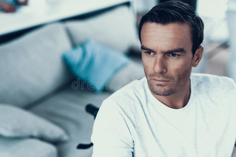 Closeup of Disabled Person With Thoughtful Look. Portrait of Handsome Serious Caucasian Brown-haired Man Sits Indoors in Wheelchair Near Sofa Wearing White T royalty free stock photography