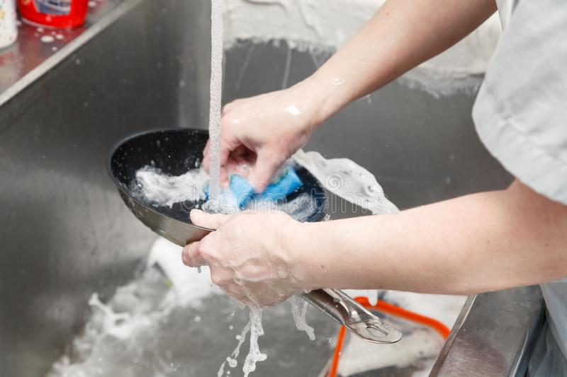 Closeup of dishwasher in uniform washes a pan with foam and a sponge under the tap water in a metal sink in the restaurant's stock image