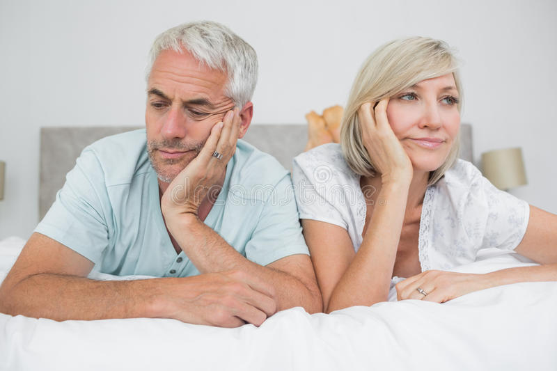 Closeup of displeased mature couple lying in bed royalty free stock image