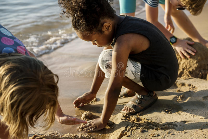 Closeup of diverse kids playing with the sand together at the be royalty free stock image