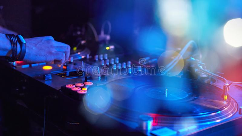Closeup Dj playing at disco progressive electric music on a beau. Tiful bokeh background with blur royalty free stock photography