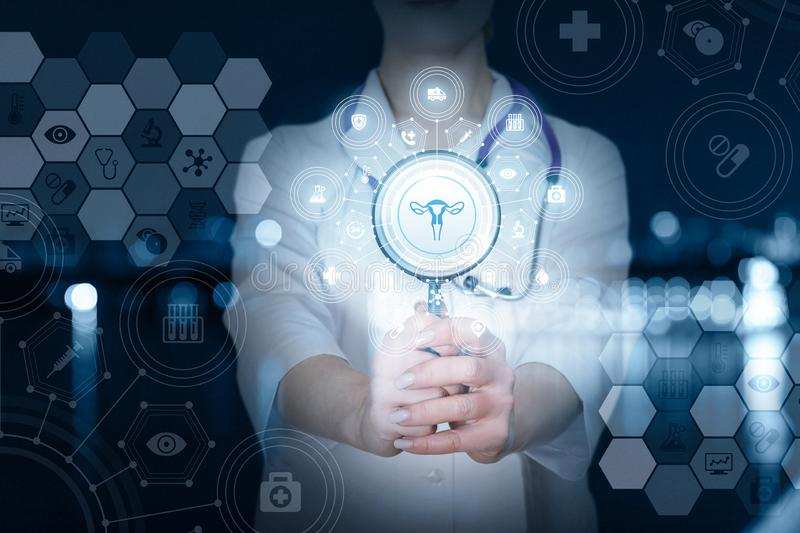 A doctor with a magnifier and a gynecology structure system. A closeup of a doctor with stethoscope showing a magnifier with a uterus image inside and total stock photography