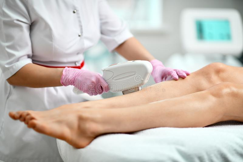 Closeup. Cosmetologist in white gown and gloves performes a procedure on patient leg. Closeup. Doctor in white gown and gloves performes a procedure epilation on stock image