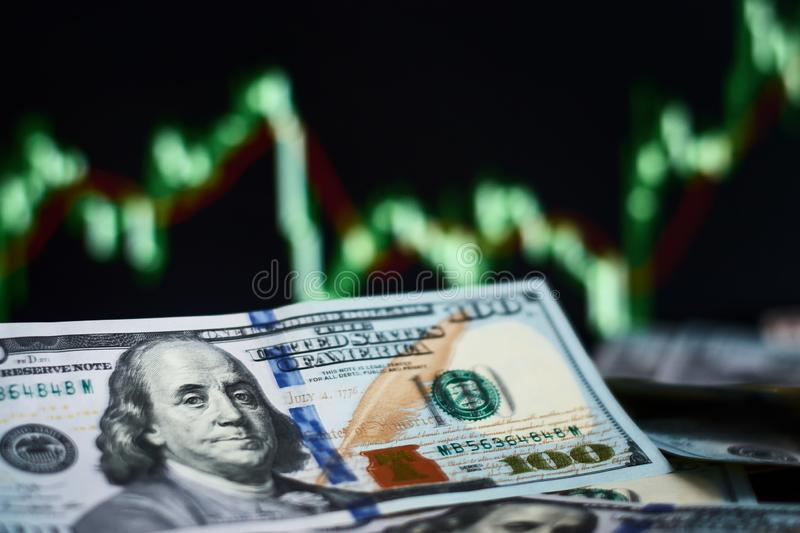 Closeup dollar banknote with screen stock exchange data graph background. Finance and a business concept royalty free stock images