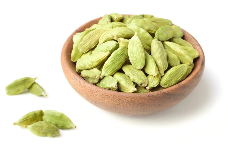 Closeup of dried cardamom in the wooden plate. Isolated stock image
