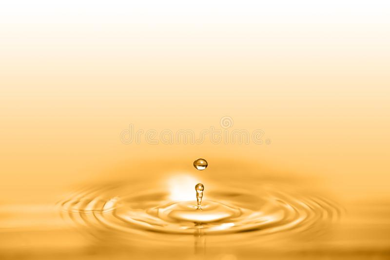 Closeup on drop of cosmetic golden oil liquid creating a circular wave. royalty free stock photo
