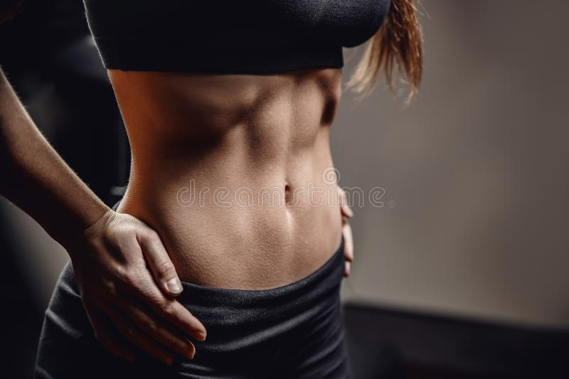 Closeup of drop of sweat on skin abdomen woman after workout. Dark background stock photos