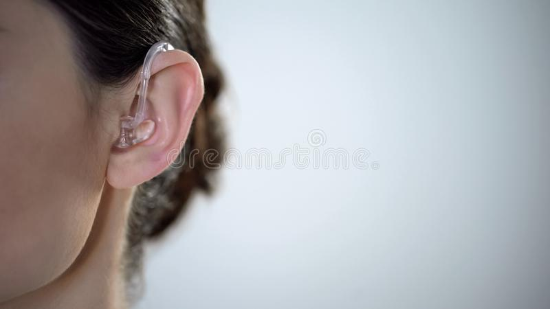 Closeup of ear with hearing aid, young deaf woman adjusting to environment stock photos