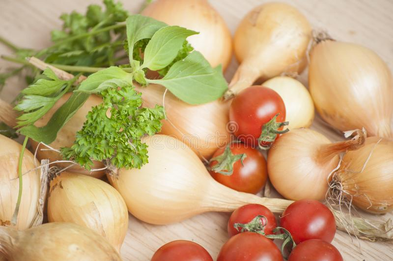 Closeup of ecologic autumn yield- whole onions, cherry tomatoes and fresh basil and parsley in sunlight royalty free stock photography