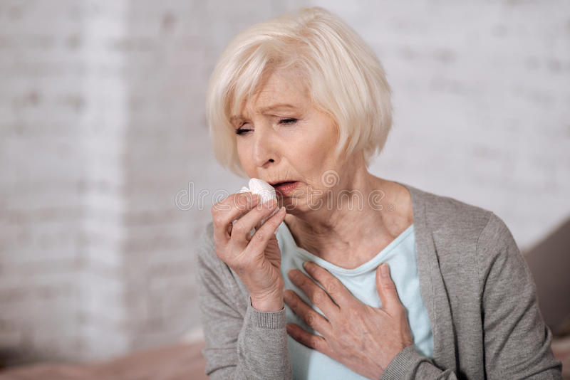 Closeup of elderly coughing woman. Bronchitis again. Close up of pretty aged woman holding napkin and coughing very strongly royalty free stock image