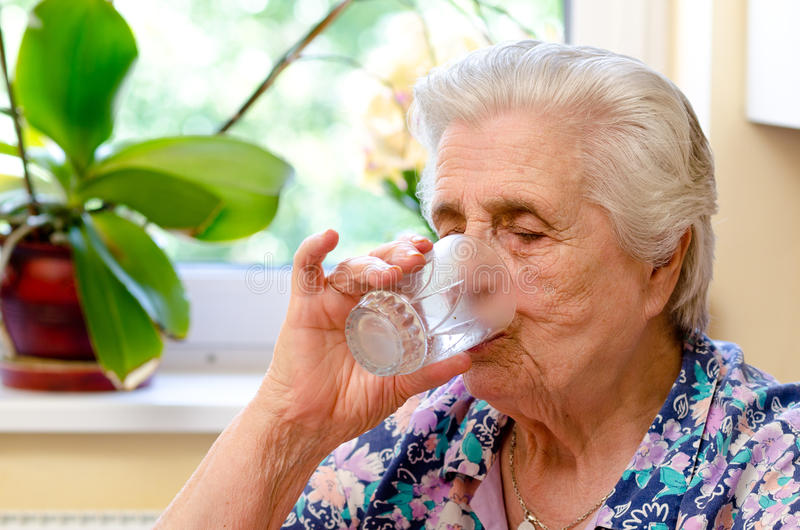 Closeup of elderly woman drinking water stock photography