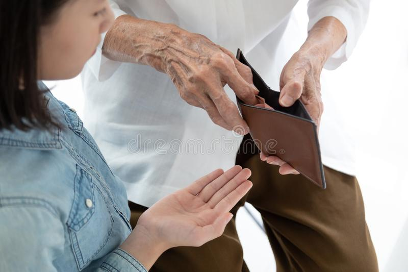 Closeup elderly woman hands open wallet,grandmother or guardian giving pocket money to granddaughter,asian little girl demanding royalty free stock photo