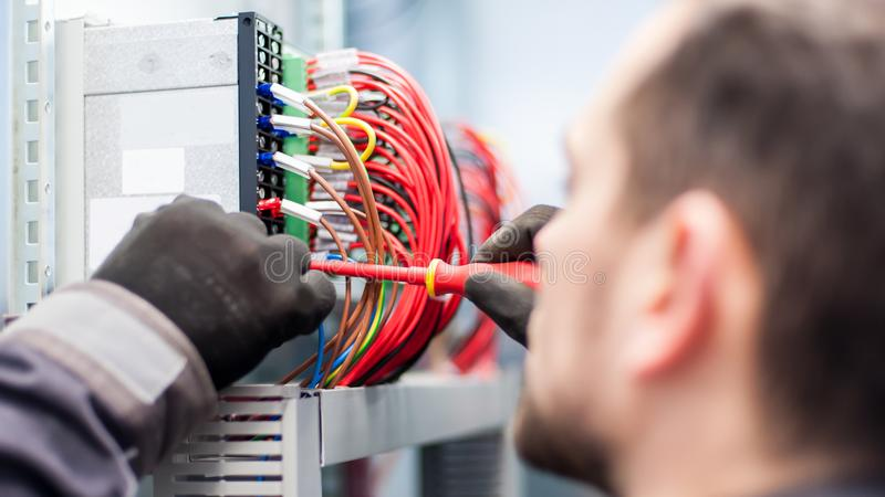 Closeup of electrician engineer works with electric cable wires stock photography