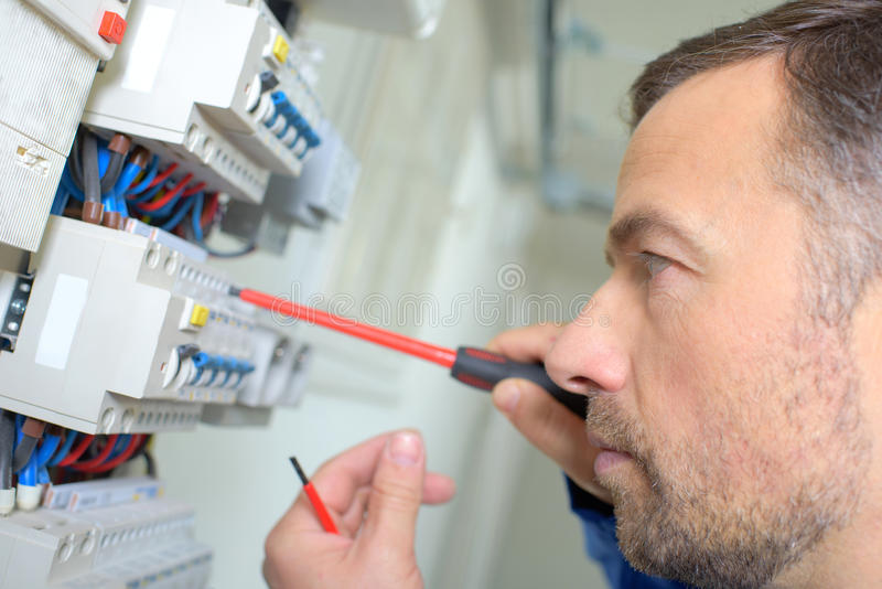 Closeup electrician working on fusebox stock images