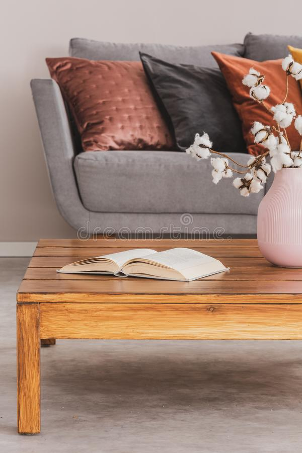 Closeup of elegant wooden coffee table in trendy living room interior with grey sofa with pillows royalty free stock image