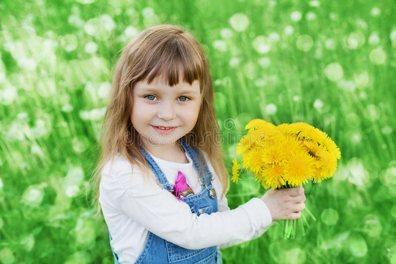 Closeup emotional portrait of cute little girl with dandelion flowers bouquet standing on a green meadow stock photo