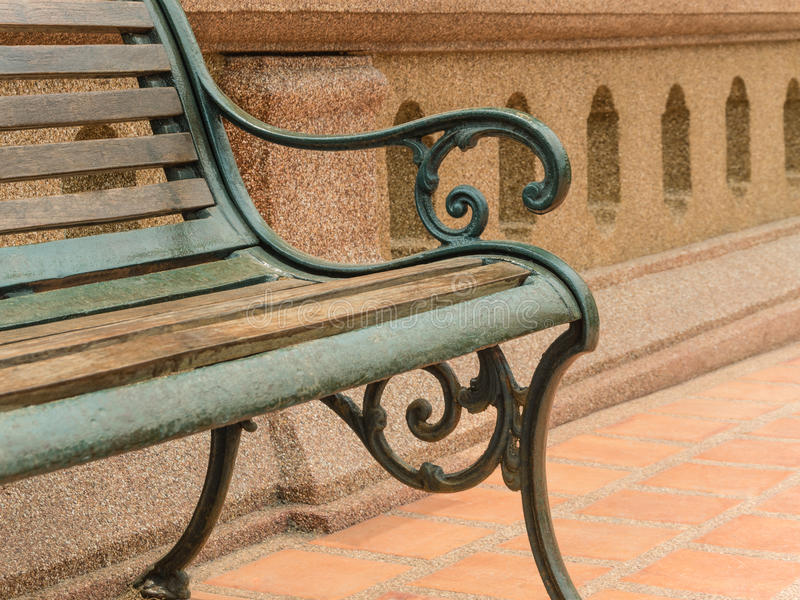 Closeup empty vintage bench in front of rugged wall royalty free stock photography
