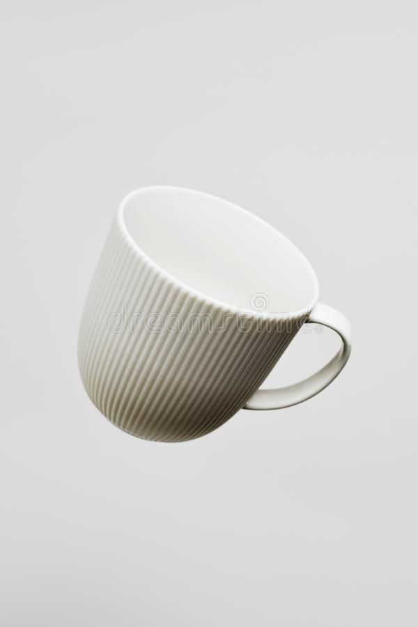 White ceramic coffee cup. Closeup of an empty white ceramic coffee cup floating on the air, against a white background with some blank space around it stock image