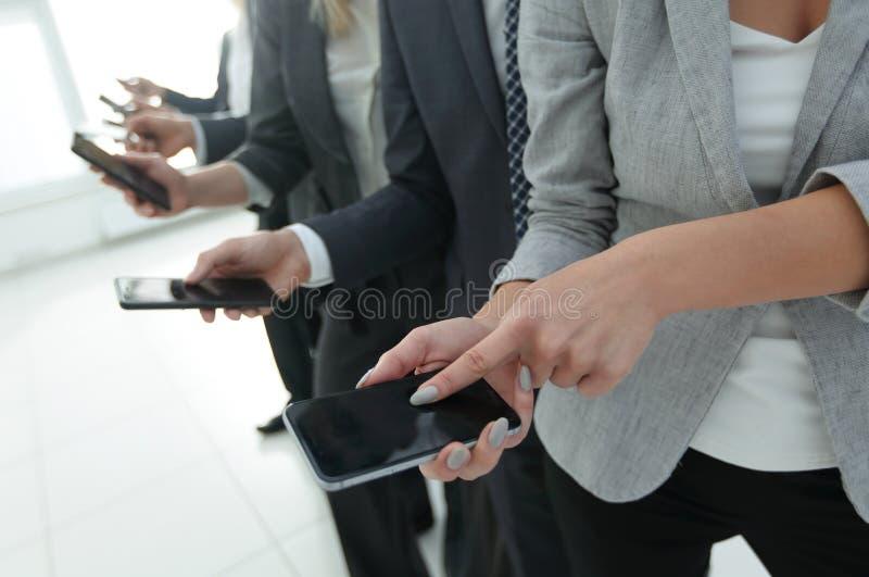 closeup en grupp av anställda med smartphones arkivbild