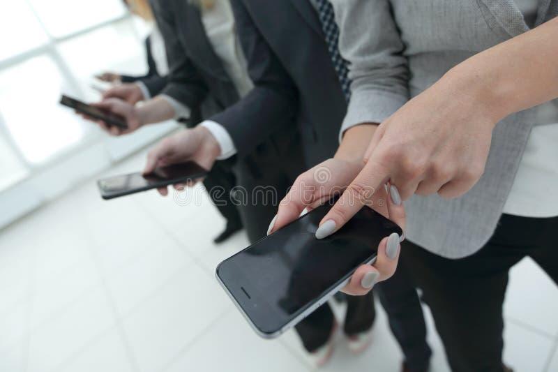 closeup en grupp av anställda med smartphones arkivbilder