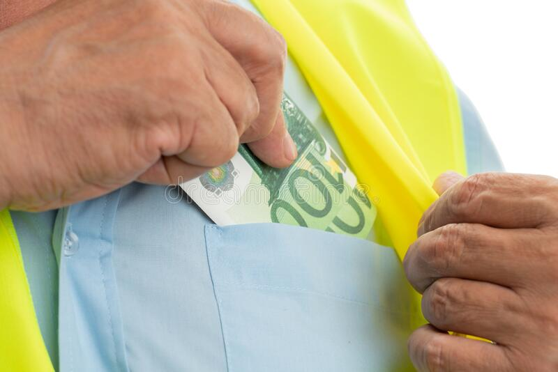 Closeup of engineer putting money in pocket royalty free stock photos