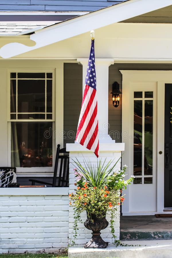 Closeup of entrance to cottage house with beautiful flowers in a pot and American flag by porch royalty free stock photo