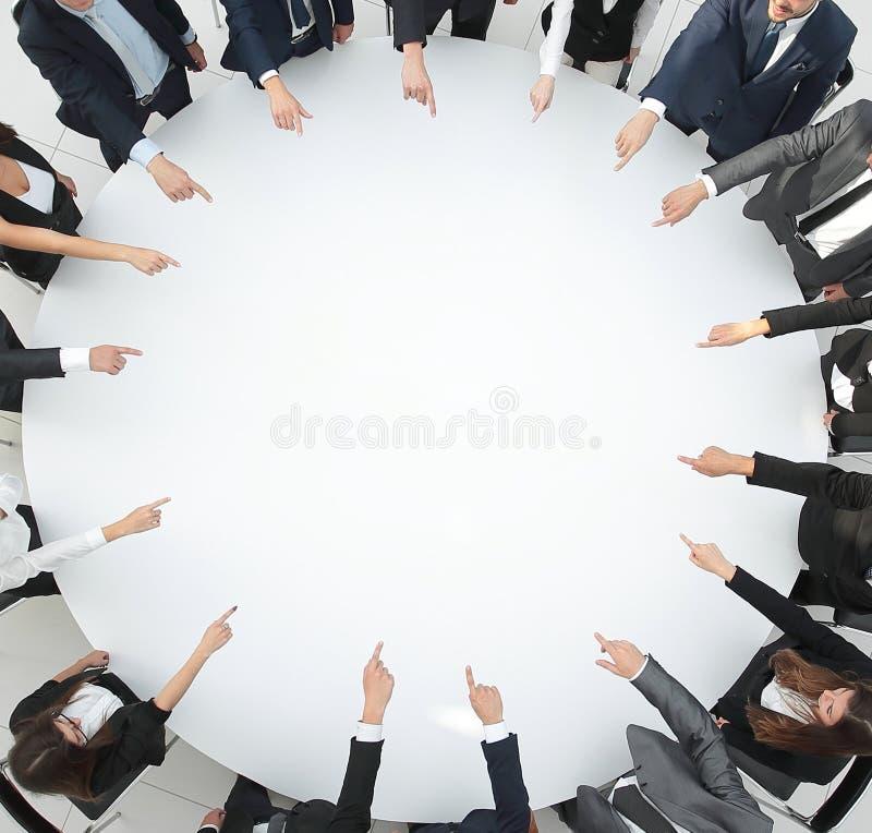closeup equipe do negócio que aponta no centro da tabela ilustração royalty free