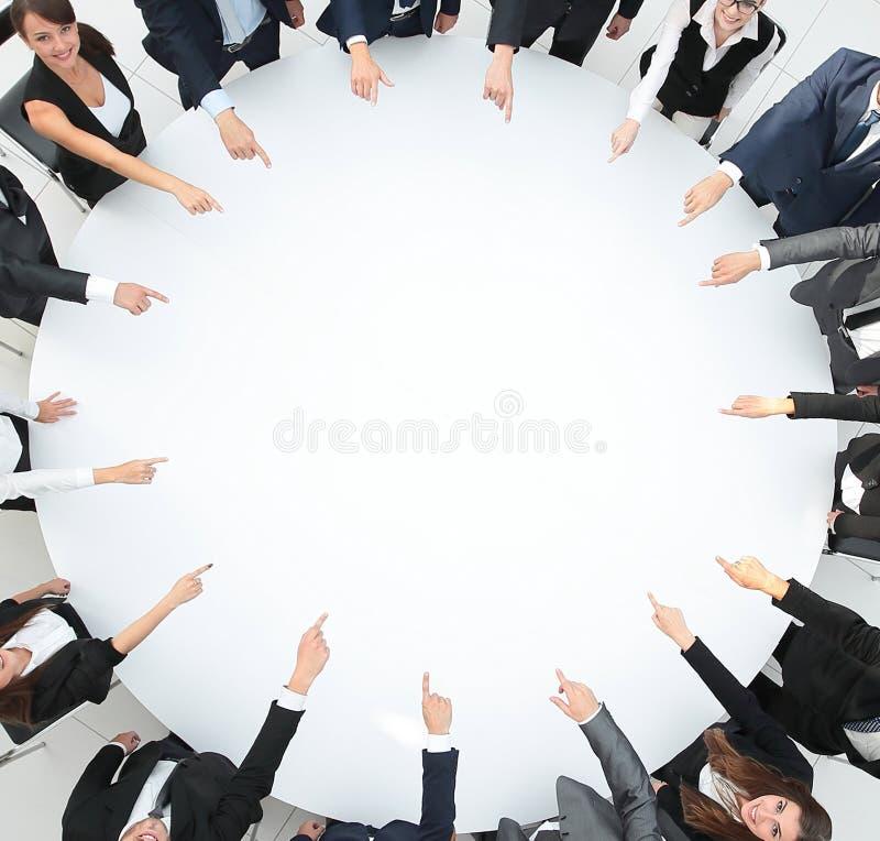 closeup equipe do negócio que aponta no centro da tabela fotografia de stock