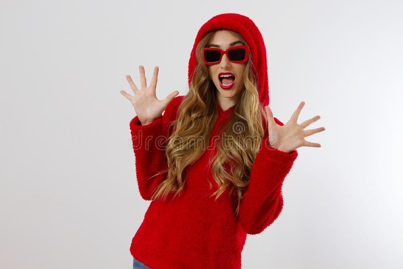 Closeup excited screaming young woman. shock, Shocked girl in red hoodie. Wow, surprised female. Fashion sweatshirt isolated royalty free stock image