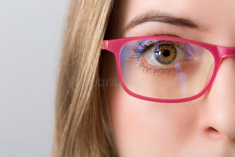 Closeup of and eye of blonde woman with pink glasses. Closeup of and eye and brown iris of blonde woman with pink glasses royalty free stock images