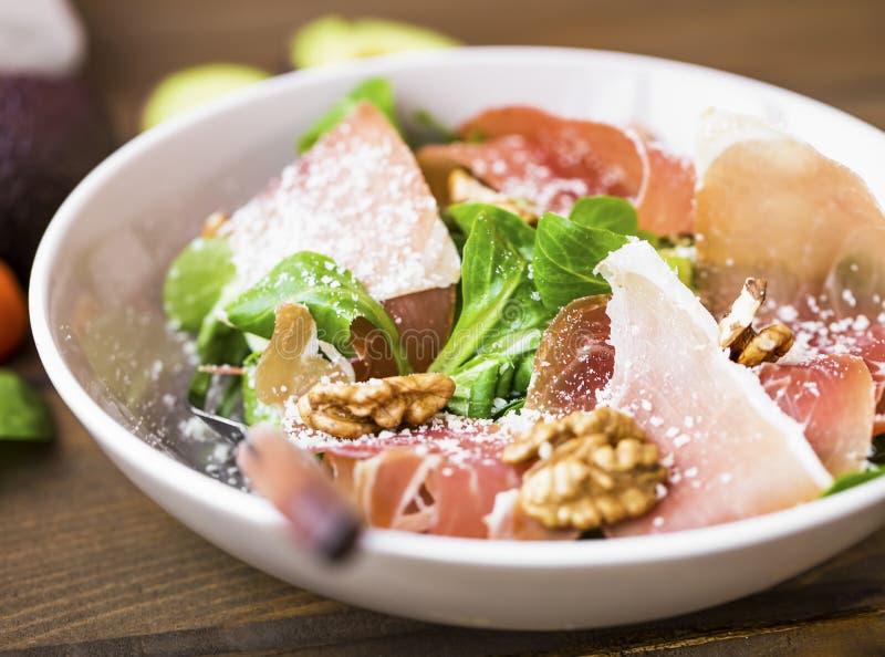 Closeup för salladbunke med prosciuttoskinka, parmesanost, valnötter och nya gröna sidor, sund italiensk gourmet- smaklig sallad royaltyfri bild
