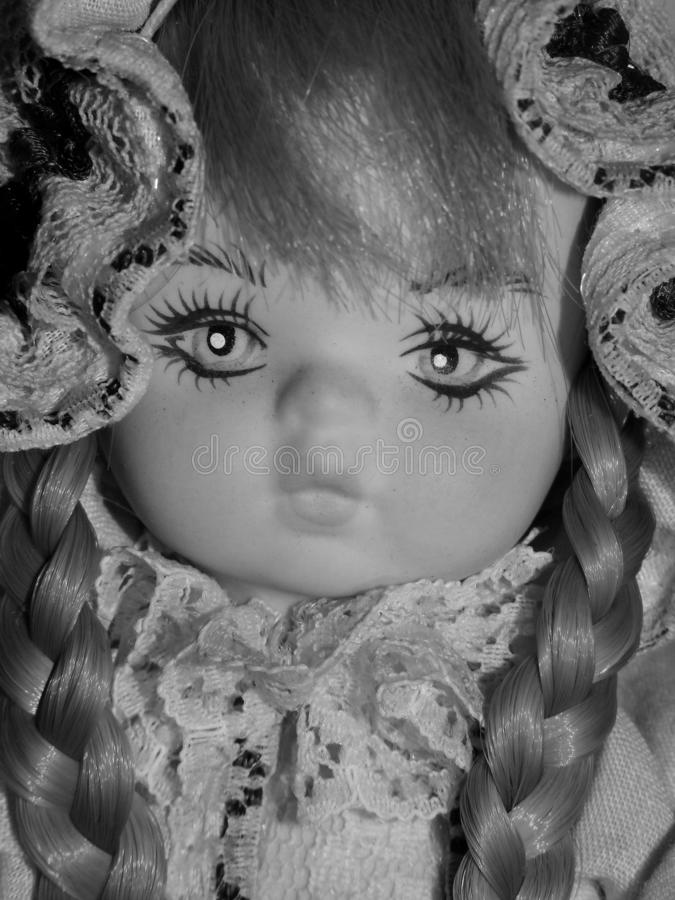 Closeup of face of blonde porcelain doll, vintage toys in black and white royalty free stock images