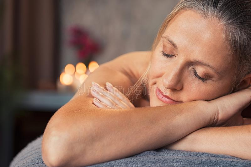 Mature woman relax at spa. Closeup face of mature woman lying on a massage table with eyes closed in a wellness center. Blonde woman lying on front and relaxing royalty free stock image