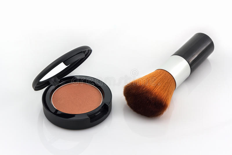 Closeup of face powder and makeup brush. royalty free stock images