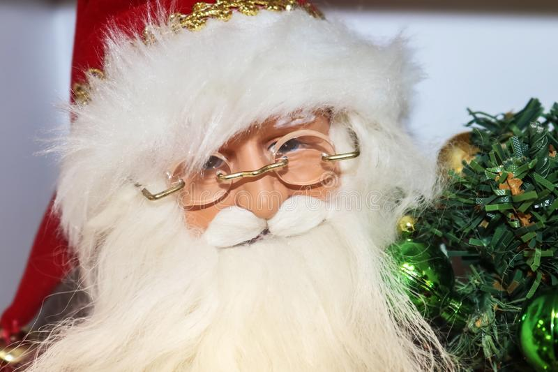 Closeup of face of Santa Claus figurine Christmas decor with glasses and with bushy beard holding green decoration royalty free stock photo