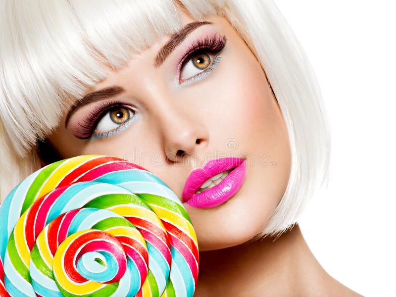 Closeup Face of a sexy girl with pink lips and multicolor sweet candy. Fashion model posing on white background stock images