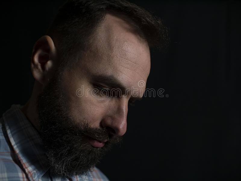Closeup face of a stylish man with a beard and mustache with a serious face looking down on a black background royalty free stock image