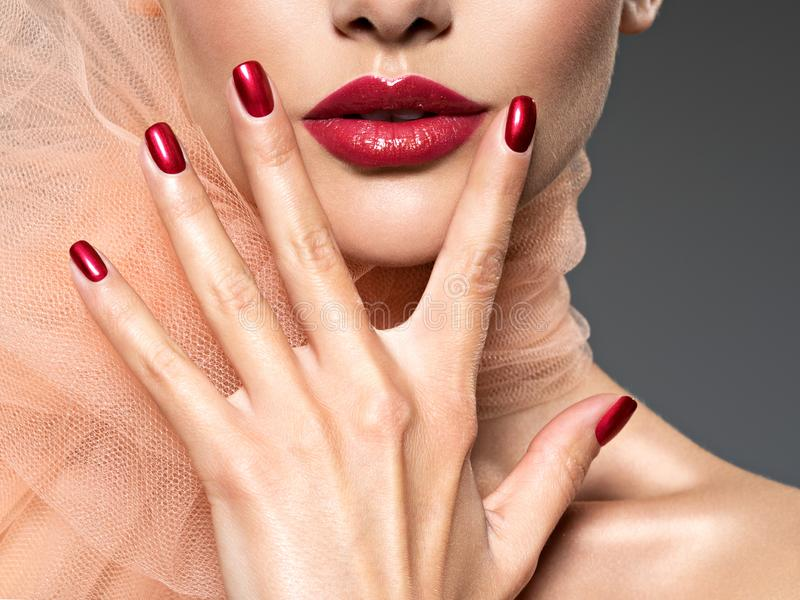 Closeup face of a  woman with red nails and lips royalty free stock photography