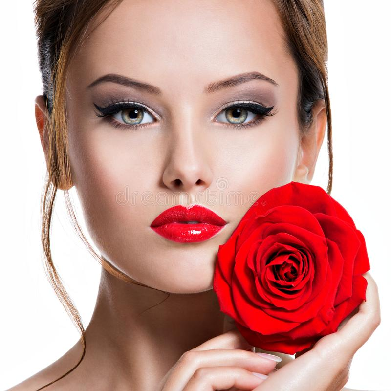 Closeup face of beautiful woman with red rose  bright makeup stock photo