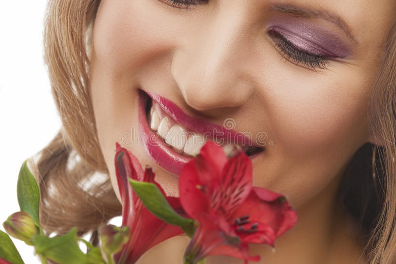 Closeup of face of young smiling woman with bunch of flowers stock photo