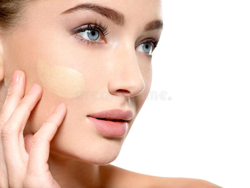 Young woman with cosmetic foundation on skin. stock image