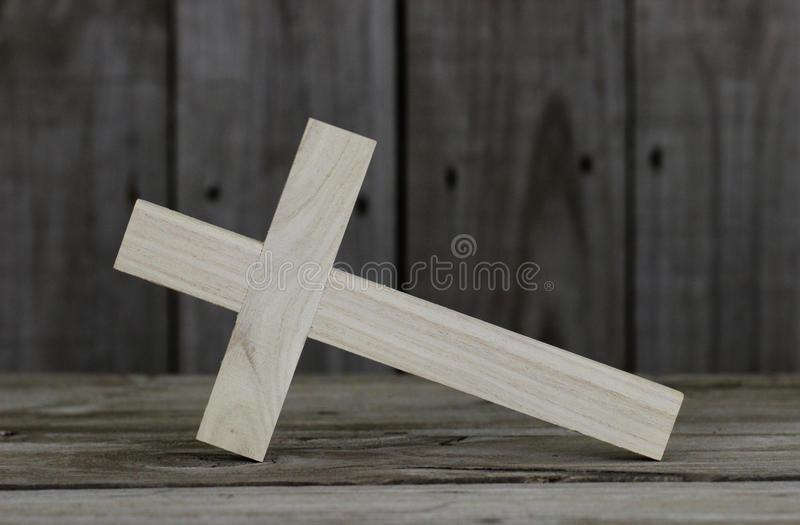 Closeup fallen wooden cross with rustic wooden background royalty free stock image